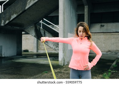 61d3bdb2a6e Sporty woman doing shoulder raises exercise with fitness resistance band.  Urban outdoor workout.