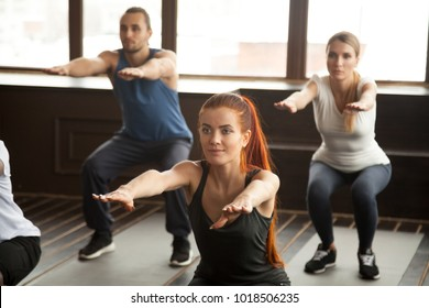 Sporty woman doing squat exercise at fitness training with young people, fit motivated group warming up muscles at strength training class working out together during routine session in gym studio