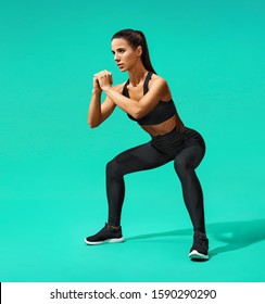 Sporty woman doing squats. Photo of muscular woman in black sportswear on turquoise background. Fitness concept