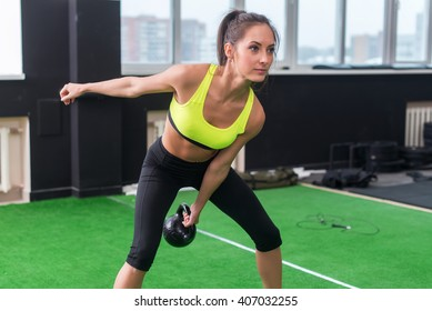 sporty woman doing work-out swinging kettlebell in gym.