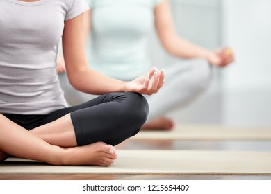 Sporty woman doing yoga in lotus pose close-up view. Mind fitness concept