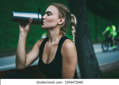 Sporty woman dressed in black tracksuit enjoying of drinking water from aluminium bottle during break after morning jogging in city park.caucasian hipster girl holding thermos during time for workout