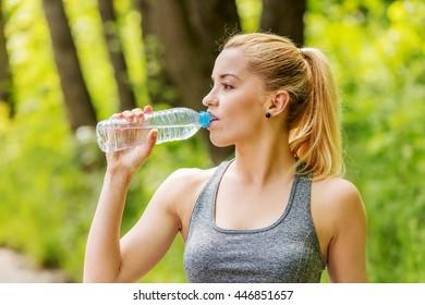Sporty woman drinking water.