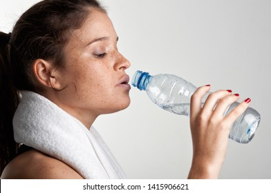 Sporty woman drinking water from a bottle after working out