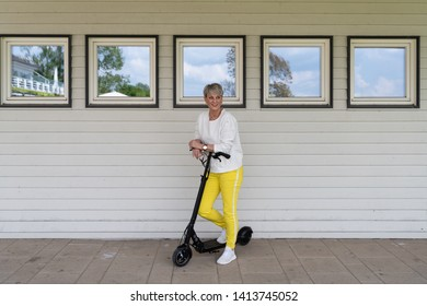 Sporty woman with e-scooter in front of house