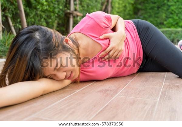 Sporty woman having heart attack at park- Angina Pectoris, Myocardial Infarction