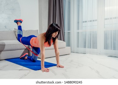 Sporty woman at home training with rubber resistance band