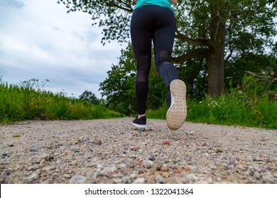 a sporty woman is jogging along a path