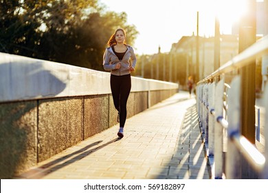 Sporty woman jogging in city to keep her body and soul in shape