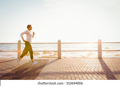 Sporty woman jogging at promenade on a sunny day