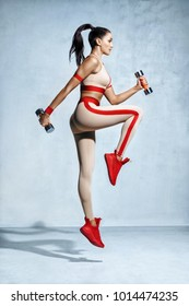 Sporty woman jumping with dumbbells. Photo of fitness model workout on grey background. Strength and motivation