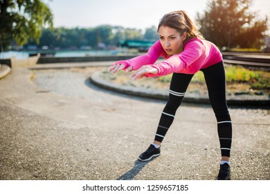 Sporty woman leaning forward and stretching hamstrings