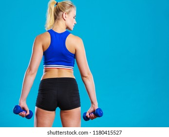 Sporty woman lifting light dumbbells weights. Fit girl exercising building muscles. Fitness and bodybuilding, back view