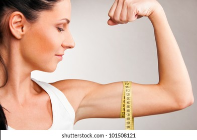 sporty woman is measuring her biceps on grey background