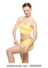 Sporty woman measuring hip by tape after fitness -  isolated on white