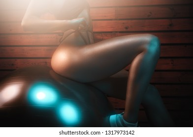 Sporty woman on exercise ball posing with her leg closeup