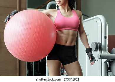 Sporty woman in pink top with beautiful body. Fitness woman on the pink fitness ball in gym. Girl with fitness ball. Beautiful girl doing exercises with ball.