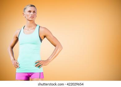 Sporty woman posing against orange vignette