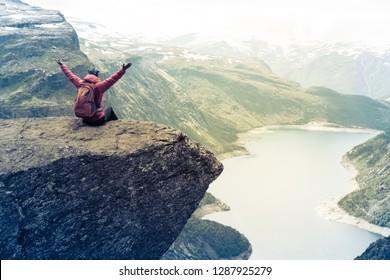 Sporty woman posing on Trolltunga. Happy hiker enjoy beautiful lake and good weather in Norway.