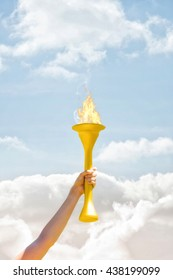 Sporty woman posing and smiling with Olympic torch against cloudy sky