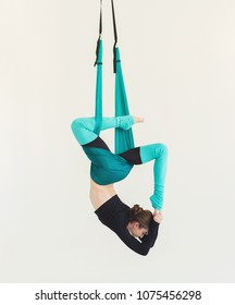 Sporty woman practicing fly yoga asana over white background in fitness studio, copy space. Health, sport, yoga concept
