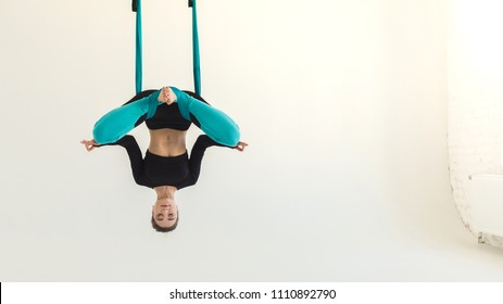 Sporty woman practicing fly yoga bat asana over white background in fitness studio, copy space, crop. Health, sport, yoga concept