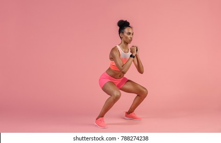 Sporty woman practicing squat exercises in studio. African woman in sportswear working out on pink background.