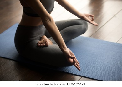 Sporty woman practicing yoga, doing Ardha Padmasana exercise, Half Lotus pose with mudra gesture, working out, wearing sportswear grey pants and top, body close up, yoga studio. Mindful life concept