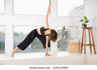 Sporty woman practicing yoga at home