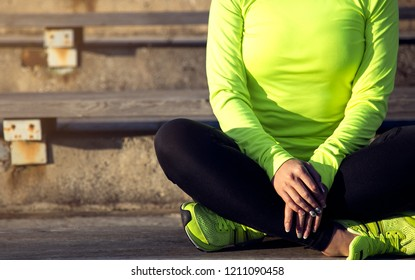 Sporty woman resting outside after workout. Focused on hands.