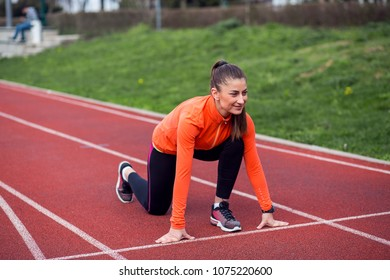 Sporty woman runner in start position