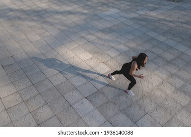 Sporty woman runner in training on grey sidewalk . Photo of attractive woman in fashionable sportswear. Dynamic movement. Top view. Sun spot. Sport and healthy lifestyle. Place for text.