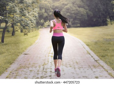Sporty woman running on road at sunrise. Fitness and workout wellness concept