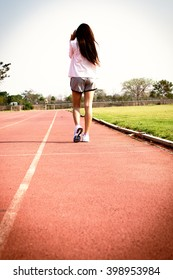 Sporty woman running on track