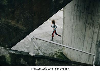 Sporty woman running on winter rainy day. Urban female athlete exercising on asphalt.