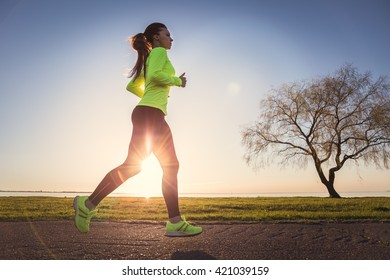 Sporty woman running at sunset. Fitness and workout wellness concept. Sports outdoors.