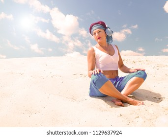 Sporty woman sitting in Lotus position in the desert