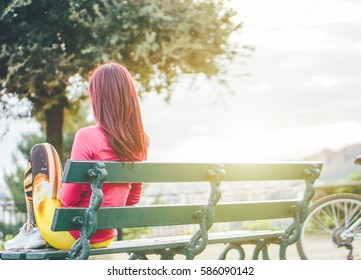 Sporty woman sitting on a bench admiring the view in a beautiful park outdoor - Depressed girl sitting alone watching the city from the hills - Sportswoman work out taking a break - Soft focus on girl