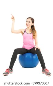 Sporty woman sitting pilates ball pointing to copy space