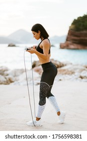sporty woman skipping rope. Sexy athletic woman rope jumping exercises outdoors on beach. Healthy lifestyle.