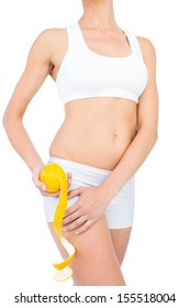 Sporty woman in sportswear holding peeled orange by her thigh on white background