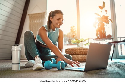 A sporty woman in sportswear is sitting on the floor with dumbbells and a protein shake or a bottle of water and is using a laptop at home in the living room. Sport and recreation concept.