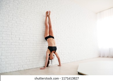 sporty woman standing on the hands near white wall