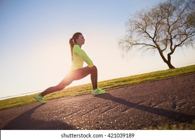 Sporty woman stretching legs before run at sunset. Fitness and workout wellness concept. Sports outdoors.