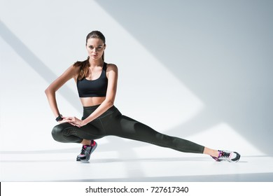 sporty woman stretching legs and looking at camera on grey