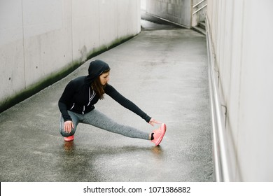 Sporty woman stretching and warming up legs before running urban fitness workout. Sport and healthy lifestyle concept. Female athlete exercising outside.