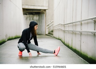 Sporty woman stretching and warming up legs for running urban fitness winter workout. Sport and healthy lifestyle concept. Female athlete exercising outside.