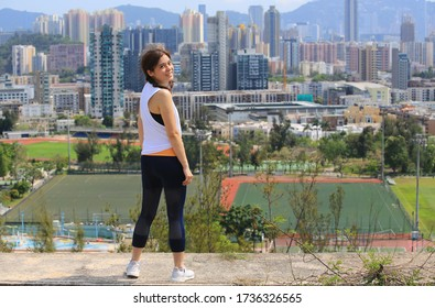 sporty woman take exercise in front of the skyline of city