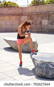 Sporty woman touching phone screen in arm sport band before running. Female athlete listening music while doing sport.
