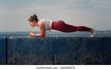 Sporty woman training core muscles at the beach. Positive Fitness female working out in summer time. Place for text.